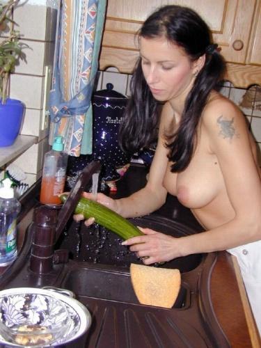 Sexy milf wast in de keuken heel onschuldig een komkommer